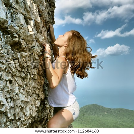 Young girl climbing vertical wall with valley view on the background - stock photo