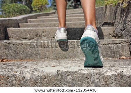 Young girl climbs on concrete stairs - stock photo