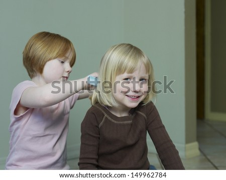 Young girl combing smiling sister's blond hair at home - stock photo