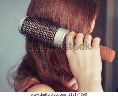 Young girl combs her hair