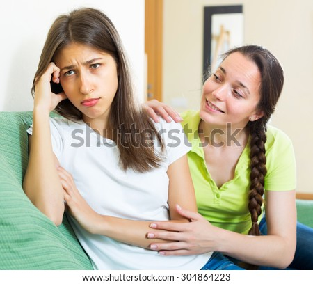 Young girl consoling her unhappy subdued sitting on the sofa