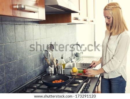 Young girl cooking vegetables