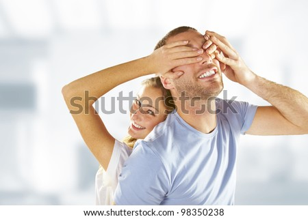 young girl covering her boyfriend eyes with both hands while relaxing on his back - stock photo