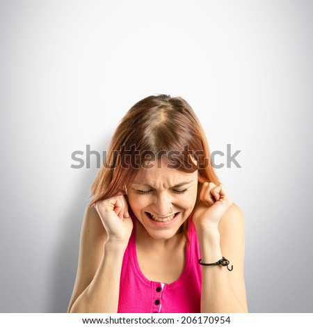 Young girl covering her ears over grey background  - stock photo