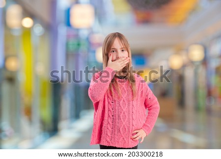 young girl covering her mouth in a shopping center
