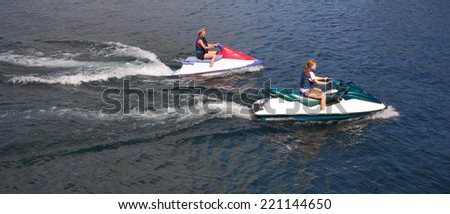 Young girl cruising on the atlantic ocean on a jet ski   - stock photo