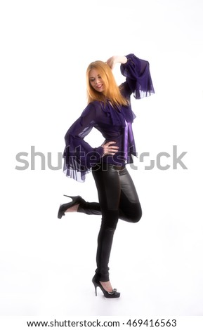 Young girl dancing and posing on a white background in black pants