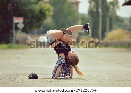 Young girl dancing breakdance on the street - stock photo