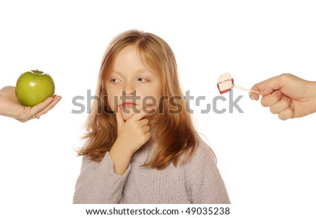 Young girl deciding between apple and sucker (looking at apple) - stock photo