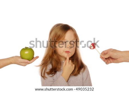Young girl deciding between apple and sucker (looking at sucker) - stock photo