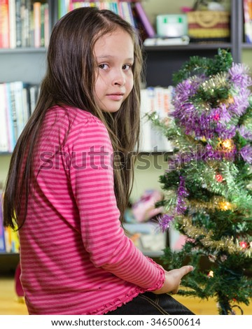 Young girl decorating Christmas tree looking at camera - stock photo