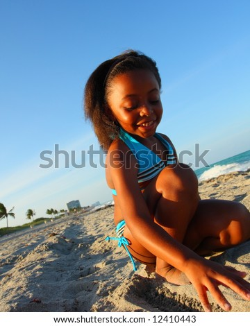 Young girl digging in the sand - stock photo