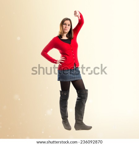 Young girl doing a bad signal over ocher background  - stock photo