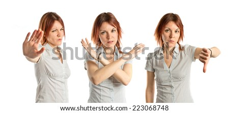 Young girl doing a bad signal over white background  - stock photo