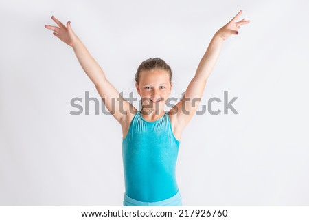 Young girl doing a gymnastics salute to the camera - stock photo