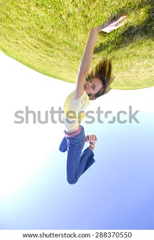 Young girl doing cartwheel across green grass on top of the world - stock photo