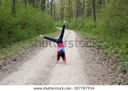 Young girl doing cartwheel in spring forest - stock photo