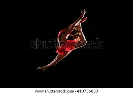 young girl doing gymnastics on the black background