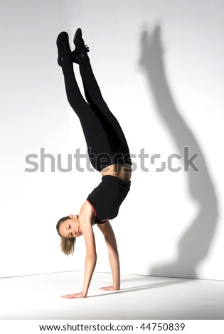 Young girl doing gymnastics over white with a shadow.