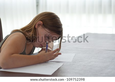 Young girl doing homework at table