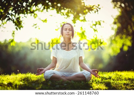 Young girl doing yoga in the park - stock photo
