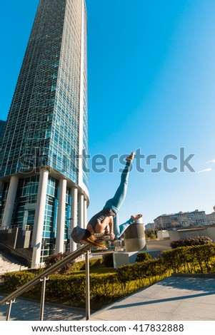 Young girl doing yoga outdoors in a city on the background of skyscrapers - stock photo