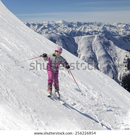 Young girl, downhill skier going down steep Alpine slope. Concept of enjoying winter activities by kids and families. - stock photo