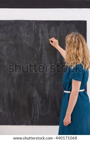 Young girl drawing on a black background. Business woman writting on the board. Teacher hand drawing on chalkboard. Education and idea concept. - stock photo