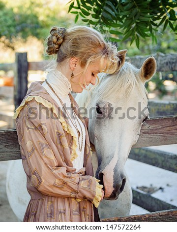 Young Girl dressed in 1800s Vintage Clothing petting horse - stock photo