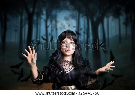 young girl dresses as a witch in a creepy forest - stock photo