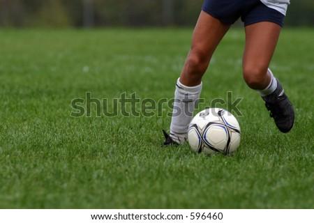 Young girl dribbling soccer ball. - stock photo
