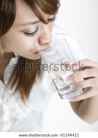 Young girl drinking a glass of mineral water - stock photo
