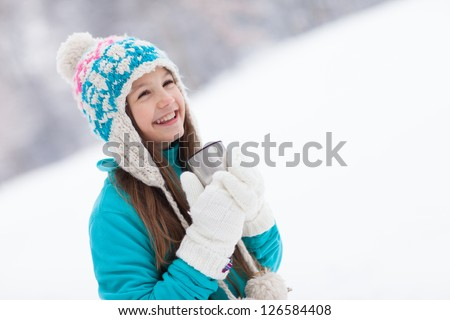 Young girl drinking from thermos cup in winter - stock photo