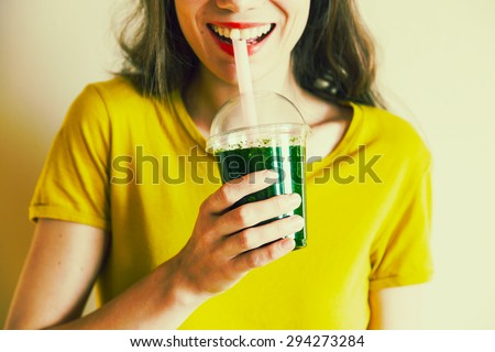 young girl drinking green cocktail with a straw - stock photo