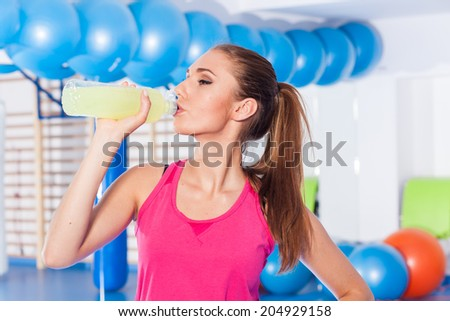 Young girl drinking isotonic drink, gym - stock photo