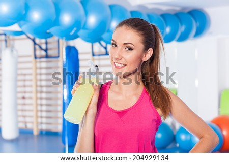 Young girl drinking isotonic drink, gym. She is happy and full of positive emotion - stock photo