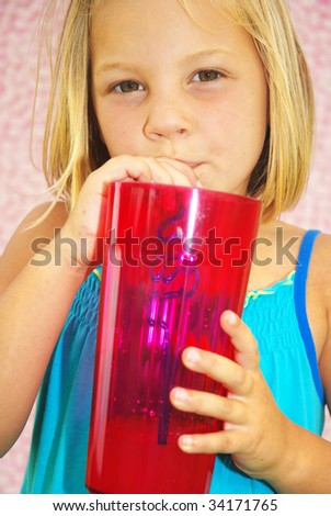 Young girl drinking out a large glass with crazy straw