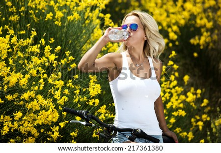Young girl drinks water from a bottle - stock photo