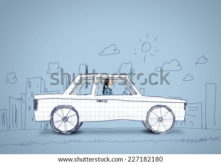 Young girl driving car made of paper - stock photo