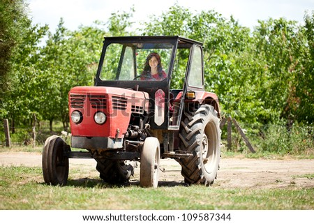 Young girl driving tractor and smiling