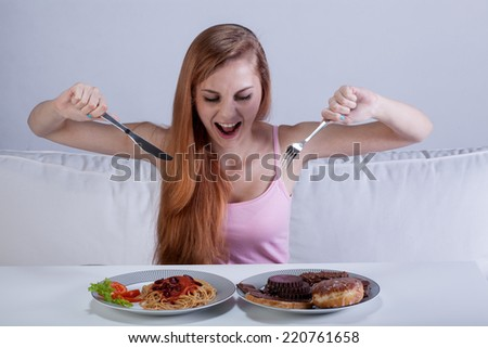 Young girl eating a lot of food at once - stock photo