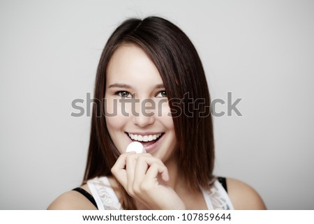 young girl eating a marshmallow with a big smile on her face - stock photo