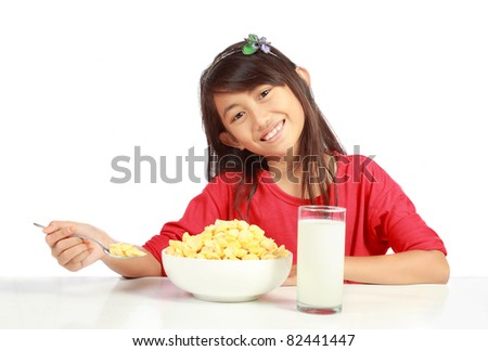 Young girl eating cereal isolated on white background - stock photo