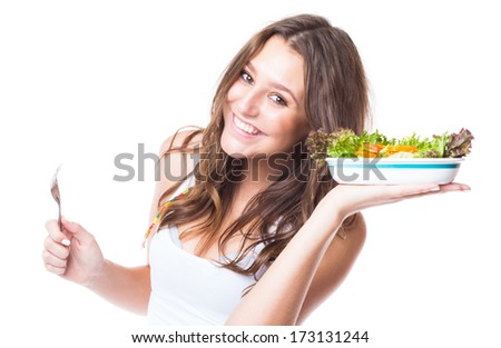 Young girl eating fresh vegetable salad on white background - stock photo