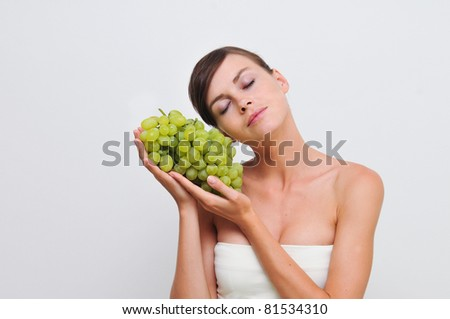 Young girl eating green grapes.