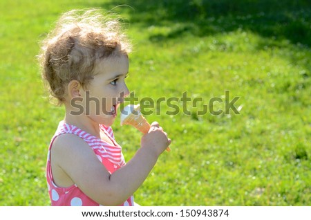 Young girl eating ice cream. Pretty child, toddler wearing a pink and white dress. She has blonde curly hair and is turned side on to camera.