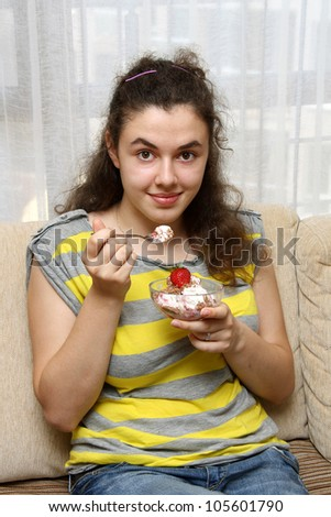 Young girl eating ice cream with strawberry