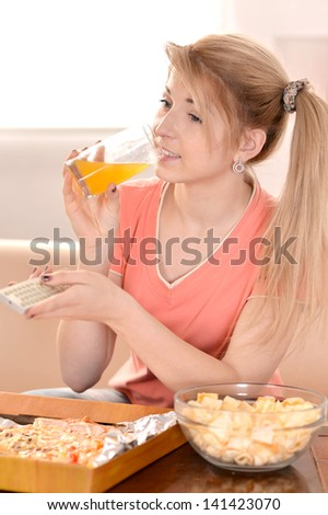 young girl eating pizza and watching TV