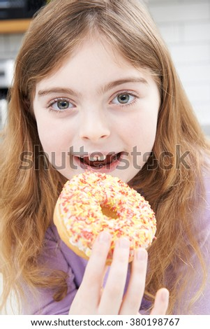 Young Girl Eating Sugary Donut For Snack