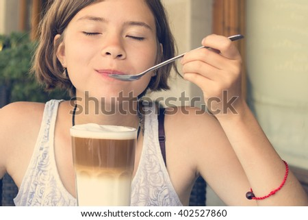 Young girl eating with a spoon smoothies. Toned - stock photo